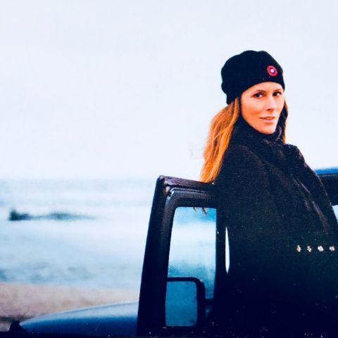 Cristina Greeven Cuomo in a black top poses a picture in front of an ocean.