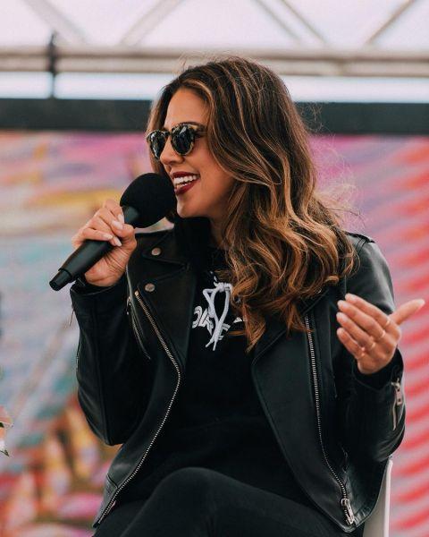 Liz Hernandez in a black jacket holding a mic.