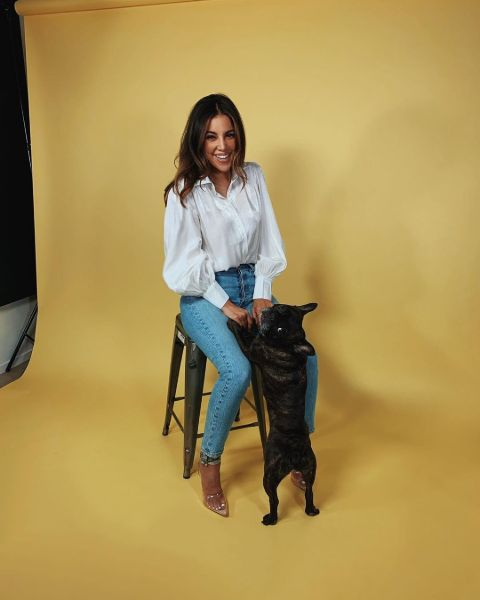 Liz Hernandez in a white t-shirt poses with her pet.