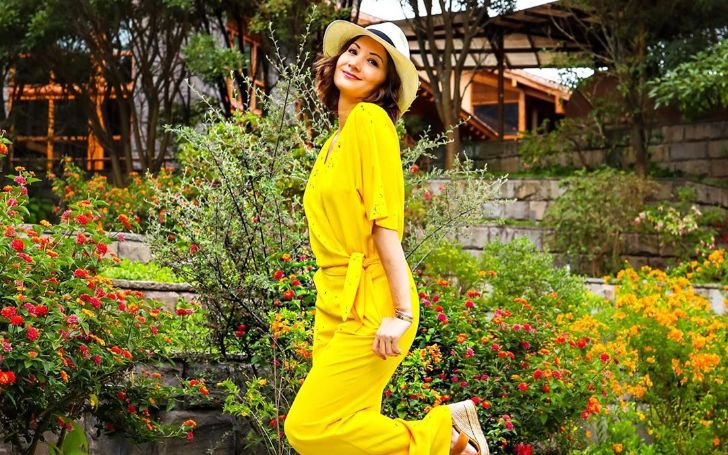 Liberte Chan in a yellow dress poses for a picture.