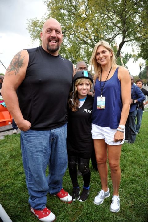 Bess Katramados in a blue top poses with son and Big Show.