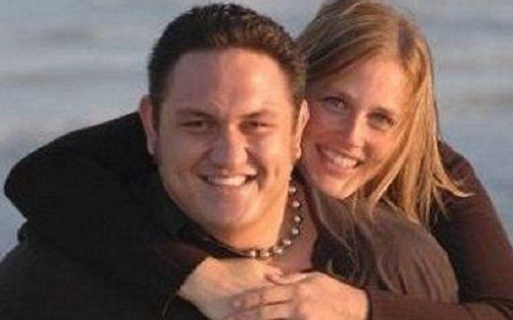 Jessica Seanoa in a black t-shirt hugging her husband Samoa Joe.