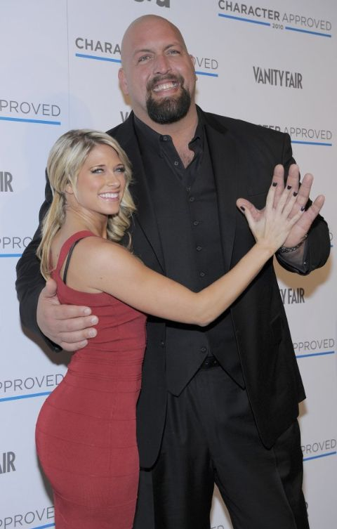 Bess Katramados in a red dress poses with Big Show at an event.