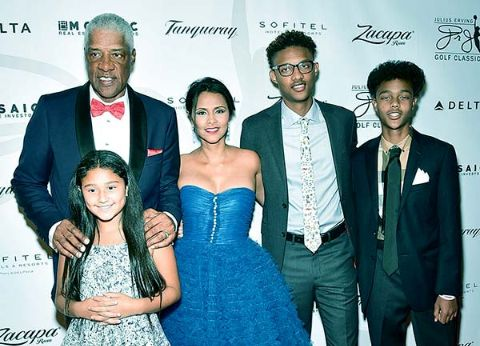 Dorys Madden in blue dress poses with husband and kids.