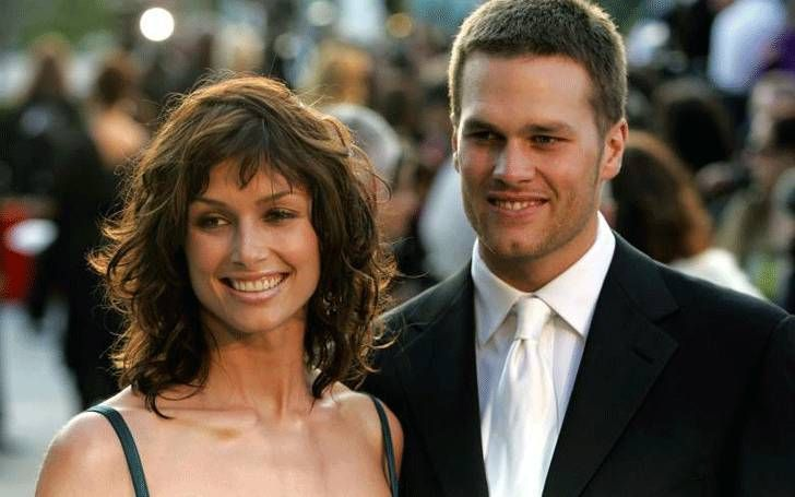 Andrew Frankel in a black suit poses with wife Bridget Moynahan.