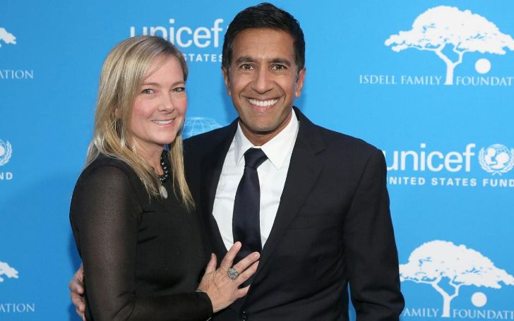 Rebecca Olson Gupta in a black dress poses with husband Dr.Sanjay Gupta.