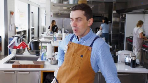 Chris Morocco in a brown apron poses in his kitchen.