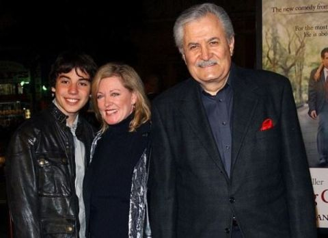 Alex Aniston in a black jacket poses with parents.
