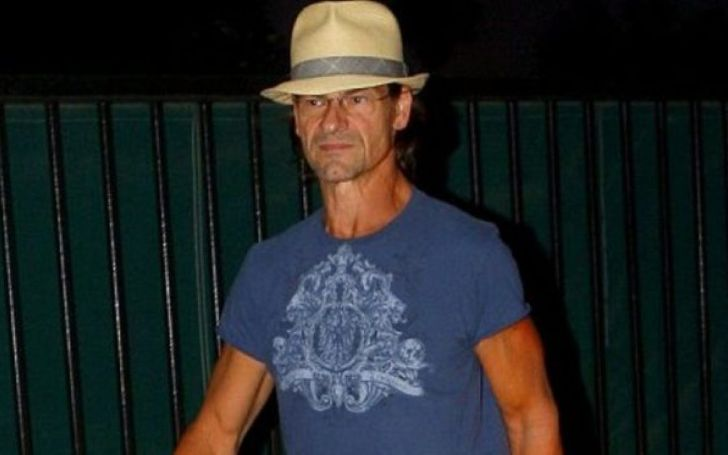 Sean Kyle Swayze in a blue t-shirt and white hat poses for a picture.