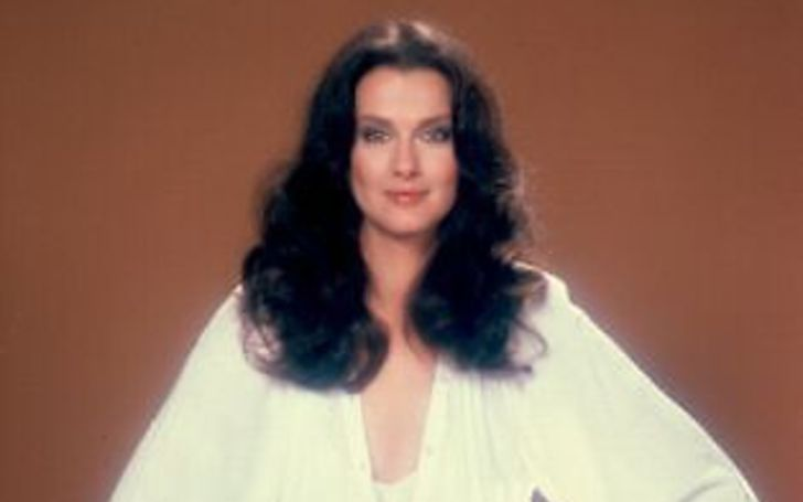 Veronica Hamel in a white dress poses for a picture.