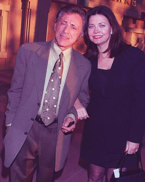 Randy Clohessy in a black dress poses with ex-husband Frankie Valli.