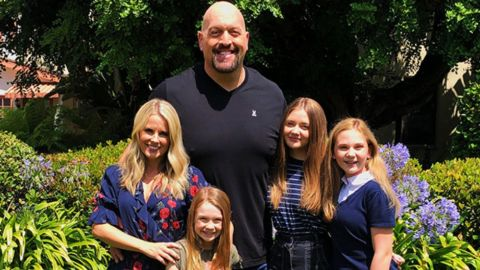 Bess Katramados in a blue top poses with Big Show and their children.