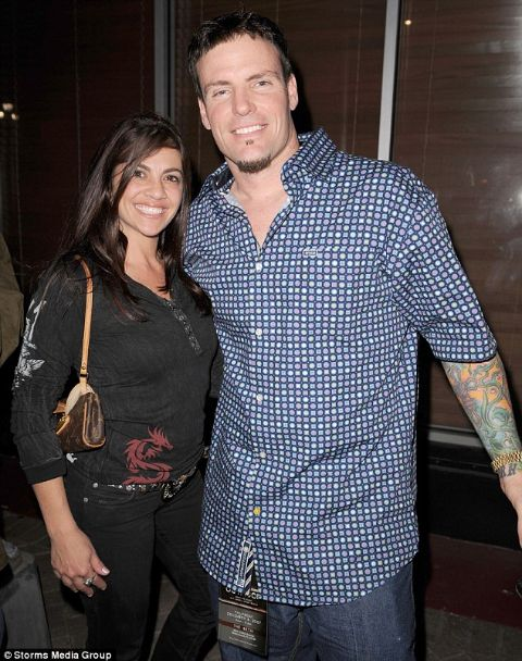 Laura Giaritta in a black dress poses with ex-husband Vanilla Ice.