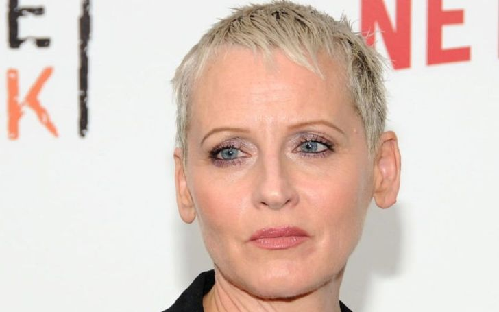Lori Petty in a black shirt poses for a photo.
