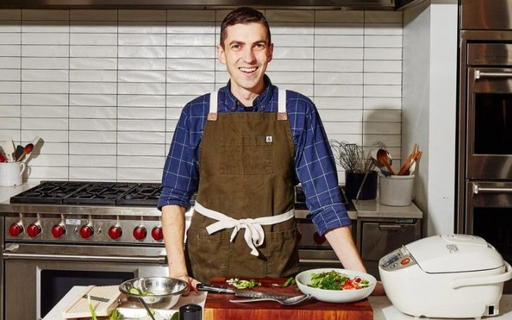 Chris Morocco poses in his kitchen in a brown apron.