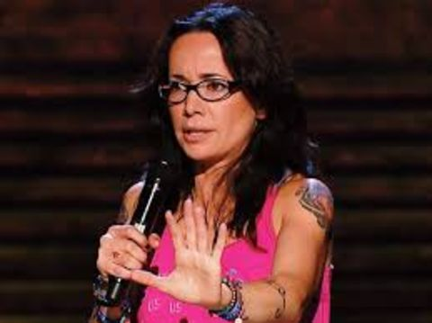 Brody Tate's wife Janeane Garofalo in a pink dress doing comedy at the stage.