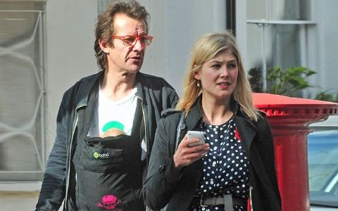 Robie Uniacke in black caught on camera with his girlfriend Rosamund Pike.