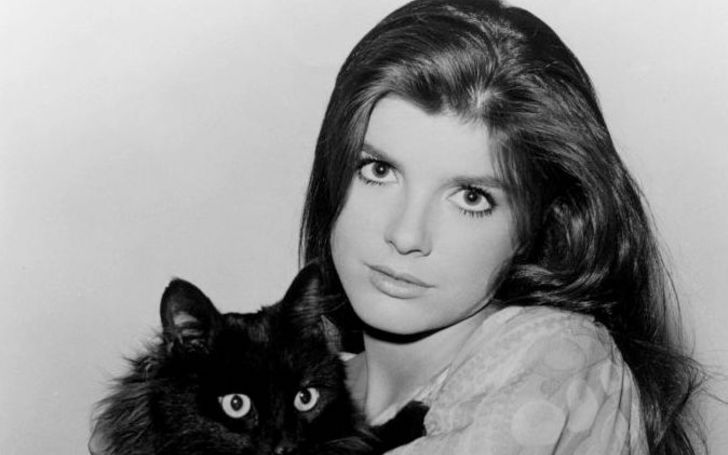 Katharine Ross poses for a picture with a black cat.