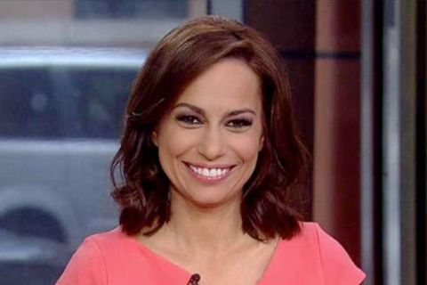 Julie Roginsky in a pink dress poses for a picture.