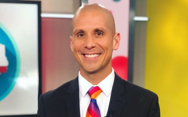 Trey Serna in a black suit poses at the news studio.