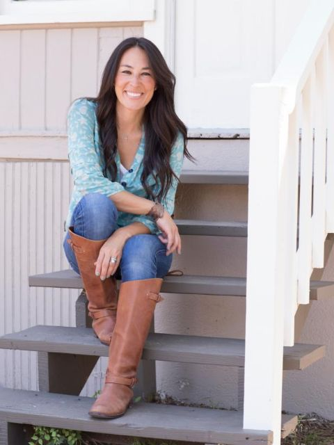 Joanna Gaines in a blue t-shirt and jeans poses for a picture.