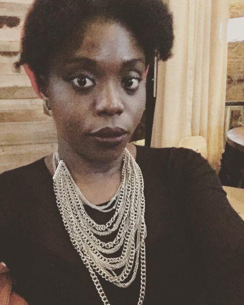 Irene Nwoye in a black dress poses for a selfie.