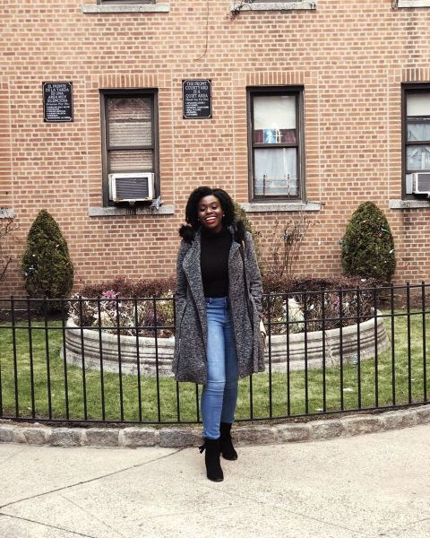 Irene Nwoye poses for a picture in a grey coat.