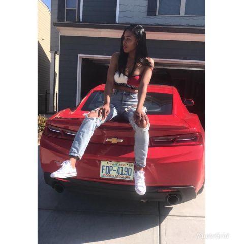 LaTaya Varner poses in her red car.