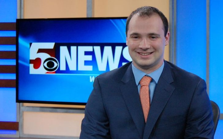 Darren Zaslau in a blue suit poses at the set of WDTV.
