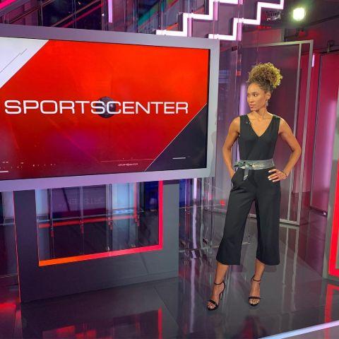 Sage Steele in a black dress in the studio of ESPN SportsCenter.