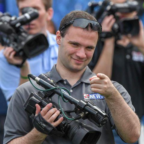 Darren Zaslau in a grey t-shirt holding a camera.