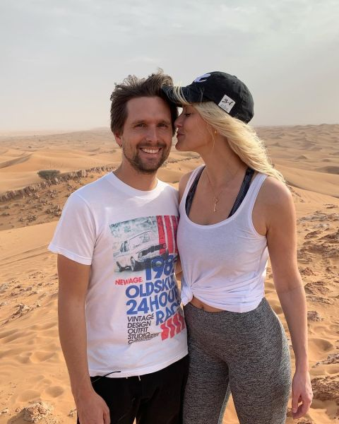 Nik Hirschi in a white t-shirt poses with wife Alex Hirschi at a desert.
