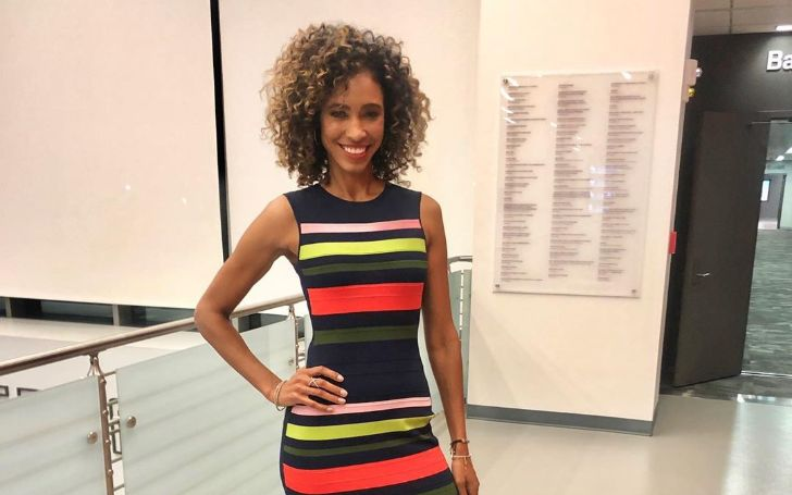 Sage Steele in a colorful dress poses for a picture.