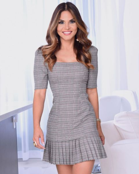 Natalia Cruz in a grey dress poses for a picture.