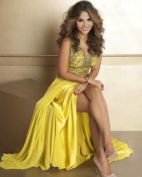 Natalia Cruz in a yellow dress poses for a picture.