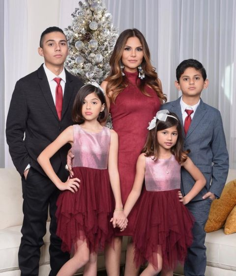 Natalia Cruz in a red dress poses with her husband and children.