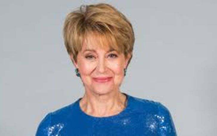 Jane Pauley in a blue dress poses for a picture.