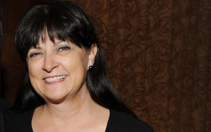 Deborah Varney in a black dress smiles at the camera.