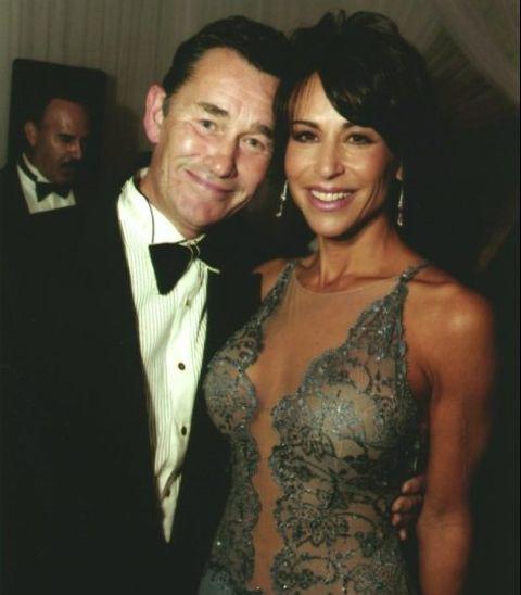Giselle Fernandez in brown dress poses with husband John Farrand.