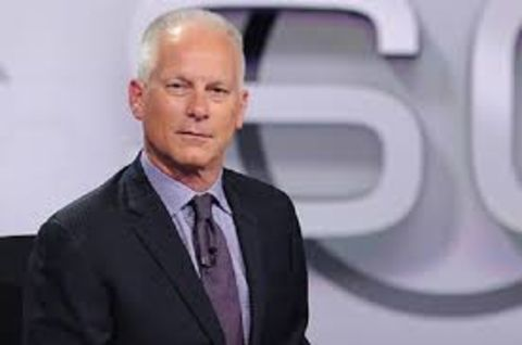 Kenny Mayne in a black suit in the sets of Sportscenter.