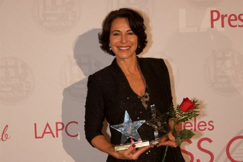 Giselle Fernandez in a black dress poses for a picture with her award.