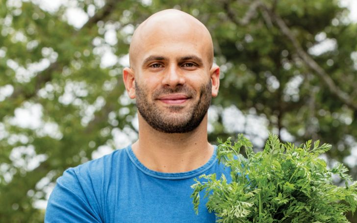 Sam Kass in a blue t-shirt poses for a picture.