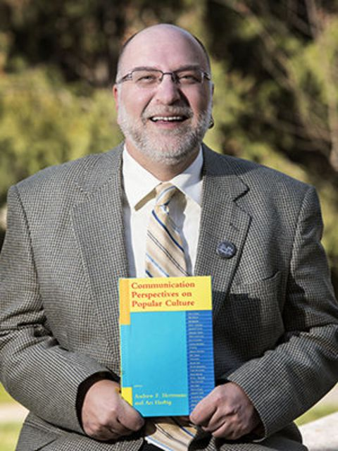 Andrew F. Herrmann in  a black suit poses with his book.