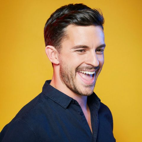 Jonathan Bailey in a black t-shirt poses for a picture
