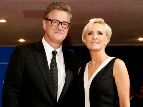 Mika Brzezinski in a black dress poses for a picture with Joe Scarborough.