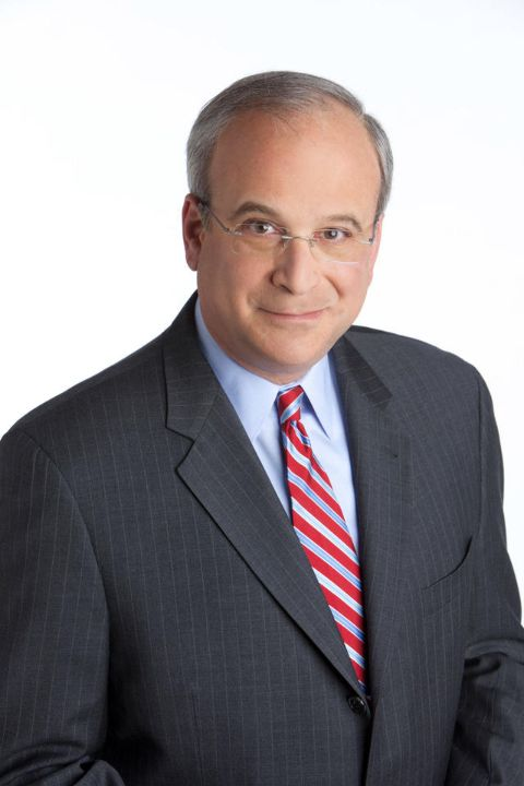 Richard Schlesinger in a black suit and red tie poses for a picture.