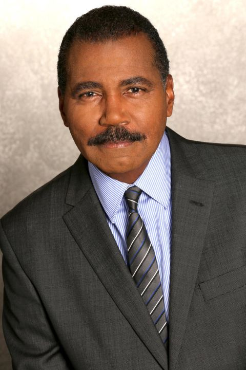 Bill Whitaker in a black suit poses for a picture.