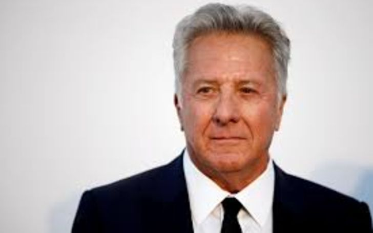 Dustin Hoffman in a black suit poses for a picture.