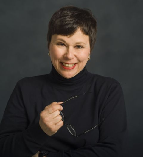 Martha Teichner in a black dress smiles at the camera.