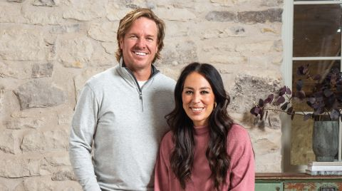 Joanna Gaines in a pink t-shirt poses a picture with husband Chip Gaines.